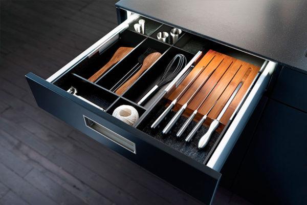 black modern cabinet open showing cooking utensils